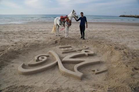كتابة الاسم باللغتين العربية والانجليزية من على شاطئ غزة المحاصرة